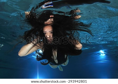 Young woman floating underwater in the pool  - stock photo