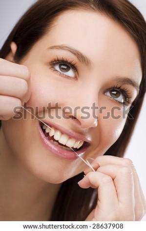 young Woman flossing teeth close up shoot - stock photo