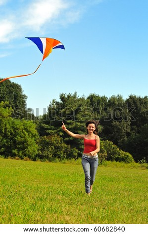 Young woman  flying a kite - stock photo