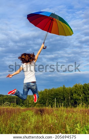 Young woman flying away with colorful umbrella