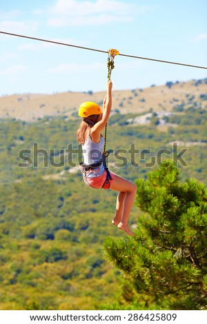 young woman flying down on zipline in mountain, extreme sport - stock photo