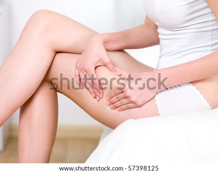 Young woman folding skin on her hips - close-up fragment - stock photo