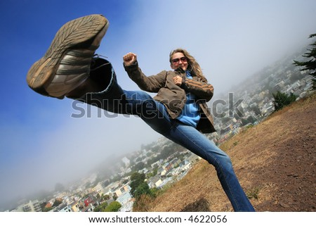 Young woman fooling around doing high kick ontop of the Kite Hill, San Francisco, California, USA. - stock photo