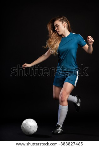 young woman football player kicking ball isolated on black backg - stock photo