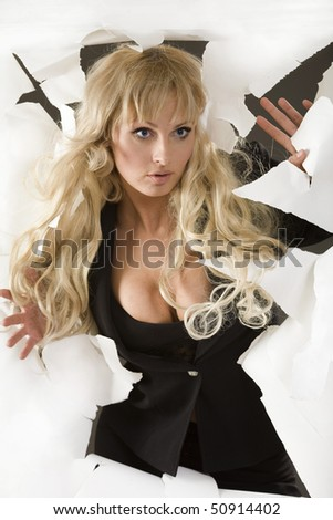 Young woman force through a paper - stock photo