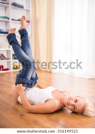 Young woman forcing to close her jeans on the floor in the room.