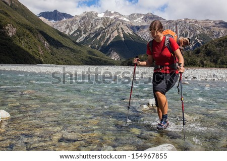 Young woman fording cold mountain stream - stock photo