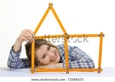 young woman forms meter stick into a house shape - stock photo