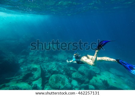 Young woman free diving in the blue waters of the popular Similan Islands in Thailand, one of the tourist attraction of the Andaman Sea.