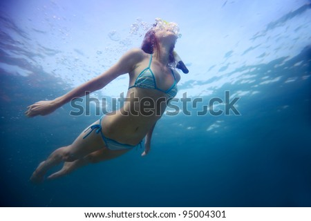 Young woman freediving in a clear sea