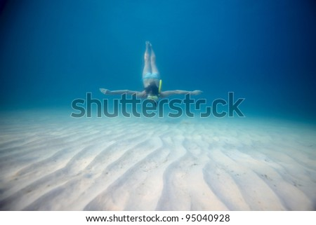 Young woman freediving in a clear sea - stock photo