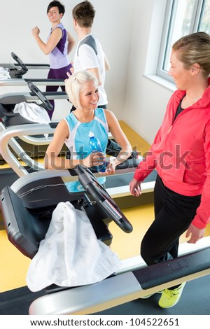 Young woman friends exercising in fitness center on treadmill machine - stock photo