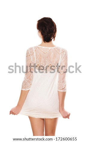 young woman from back pulling her dress on white background - stock photo