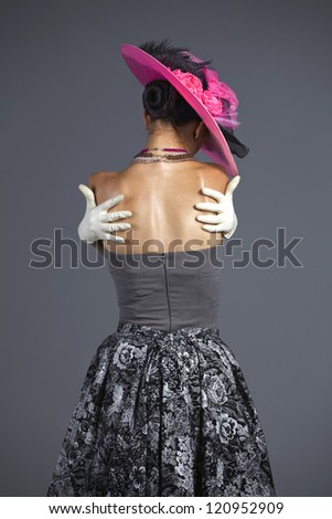 Young woman from behind vintage hat and style - stock photo