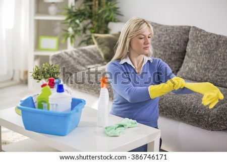 Young woman from cleaning service cleans house - stock photo