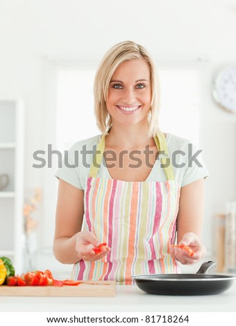 Young woman frying peppers looking into the camera in the kitchen - stock photo
