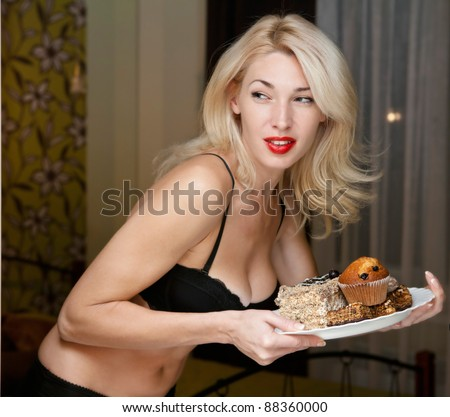 Young woman furtively at night regales cakes - stock photo