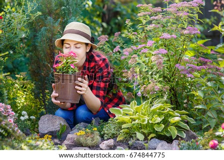 young woman gardener smelling flowers in pot with eyes closed people gardening care