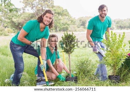 Young woman gardening for the community on a sunny day - stock photo