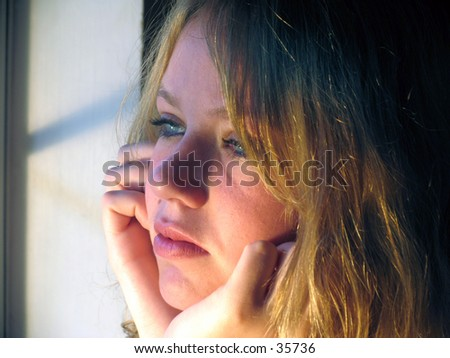 Young woman gazing out a window - stock photo