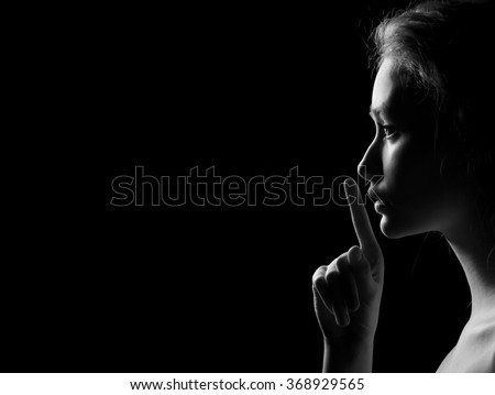 Young Woman Gesturing For Being Quiet, Shows Silence Sign In Dark Background With Copyspace, monochrome image - stock photo