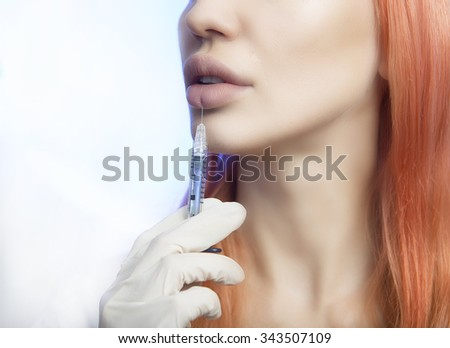Young Woman Geting Injection in her Lips. Beauty Injections - Woman wondered about methods lip augmentation in beautician office. Increase Lips by Hyaluronic acid, Contouring procedure, revitalization - stock photo