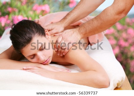 Young woman gets a massage. Eyes are closed. - stock photo