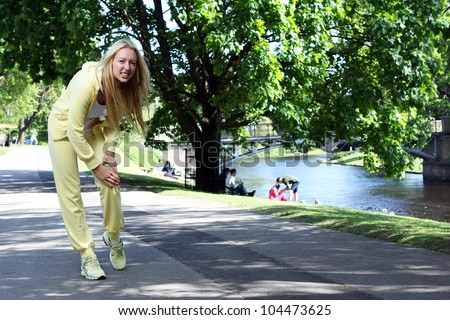 Young woman gets leg injury while working out in park - stock photo