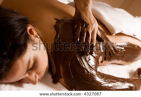 young woman getting a chocolate massage at a spa - stock photo