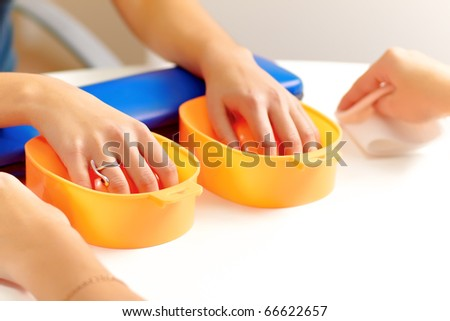 Young woman getting a manicure in a nail salon. Focus on right hand. - stock photo