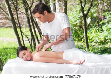 Young woman getting a massage by a handsome man - stock photo