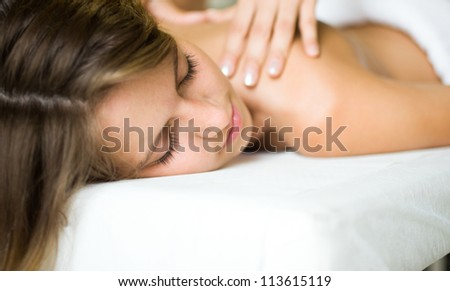 Young woman getting a massage in a spa - stock photo