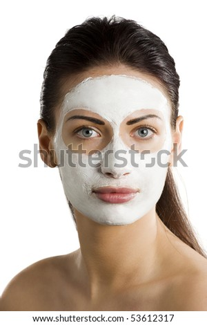 young woman getting beauty skin treatment with a cream mask on her face
