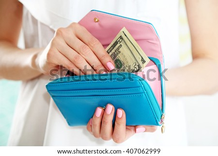 Young woman getting dollars banknotes from purse - stock photo