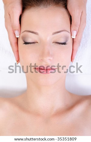 Young woman getting face massage in spa salon - stock photo