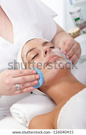 Young woman getting facial beauty treatment at beauty saloon.