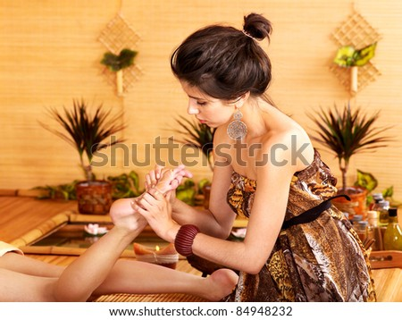 Young woman getting foot massage in bamboo spa. - stock photo