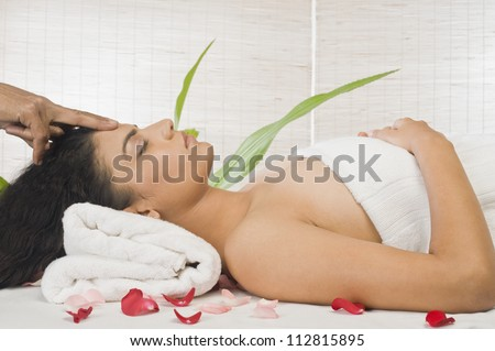 Young woman getting head massage from a massage therapist - stock photo