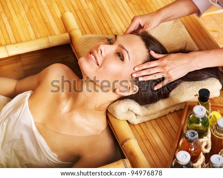Young woman getting head massage in bamboo spa. - stock photo