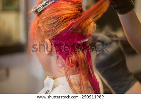 Young woman getting her hair dyed a vivid red in salon - stock photo
