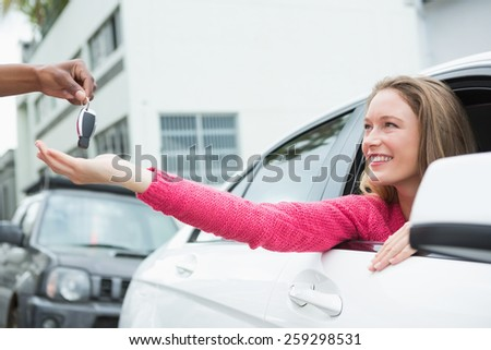 Young woman getting her new car key in her car - stock photo