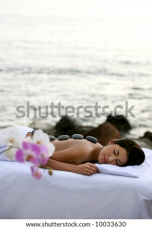 Young woman getting Lastone Therapy outdoor in the resort - stock photo