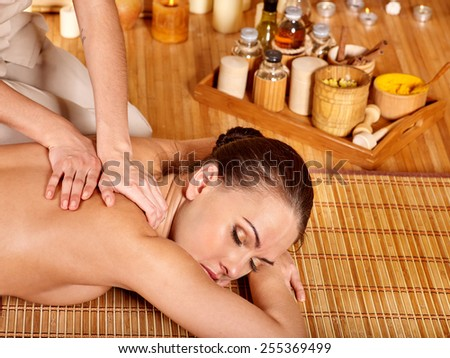 Young woman getting massage in bamboo spa. girl lying on wooden mat - stock photo