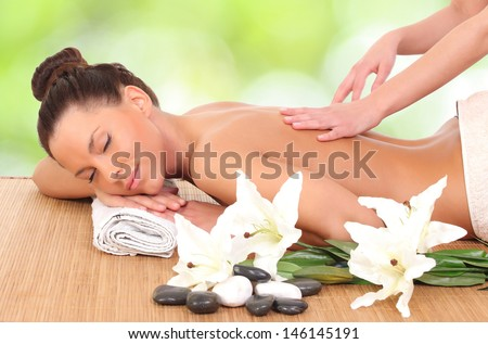 Young woman getting massage in massage salon.