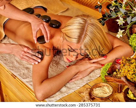 Young woman getting relaxing hot stone therapy massage .
