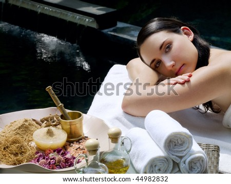 Young woman getting spa treatment at tropical resort - stock photo