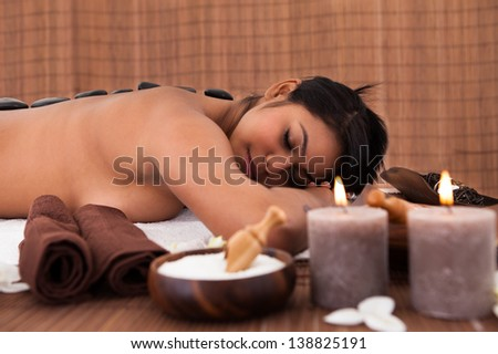 Young Woman Getting Spa Treatment With Stone Massage - stock photo
