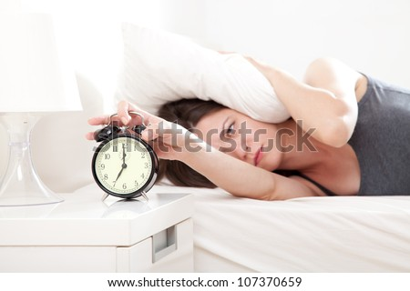 Young woman getting stressed about waking up too early, shallow depth of field, focus on foreground - stock photo