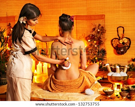 Young woman getting thai herbal massage ball. - stock photo