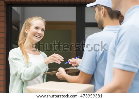 Young woman getting the delivery from the postman